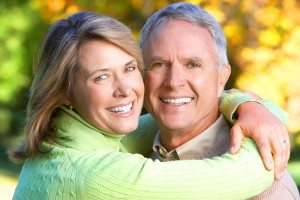 Mature Couple Embracing and Smiling with Greenery Background
