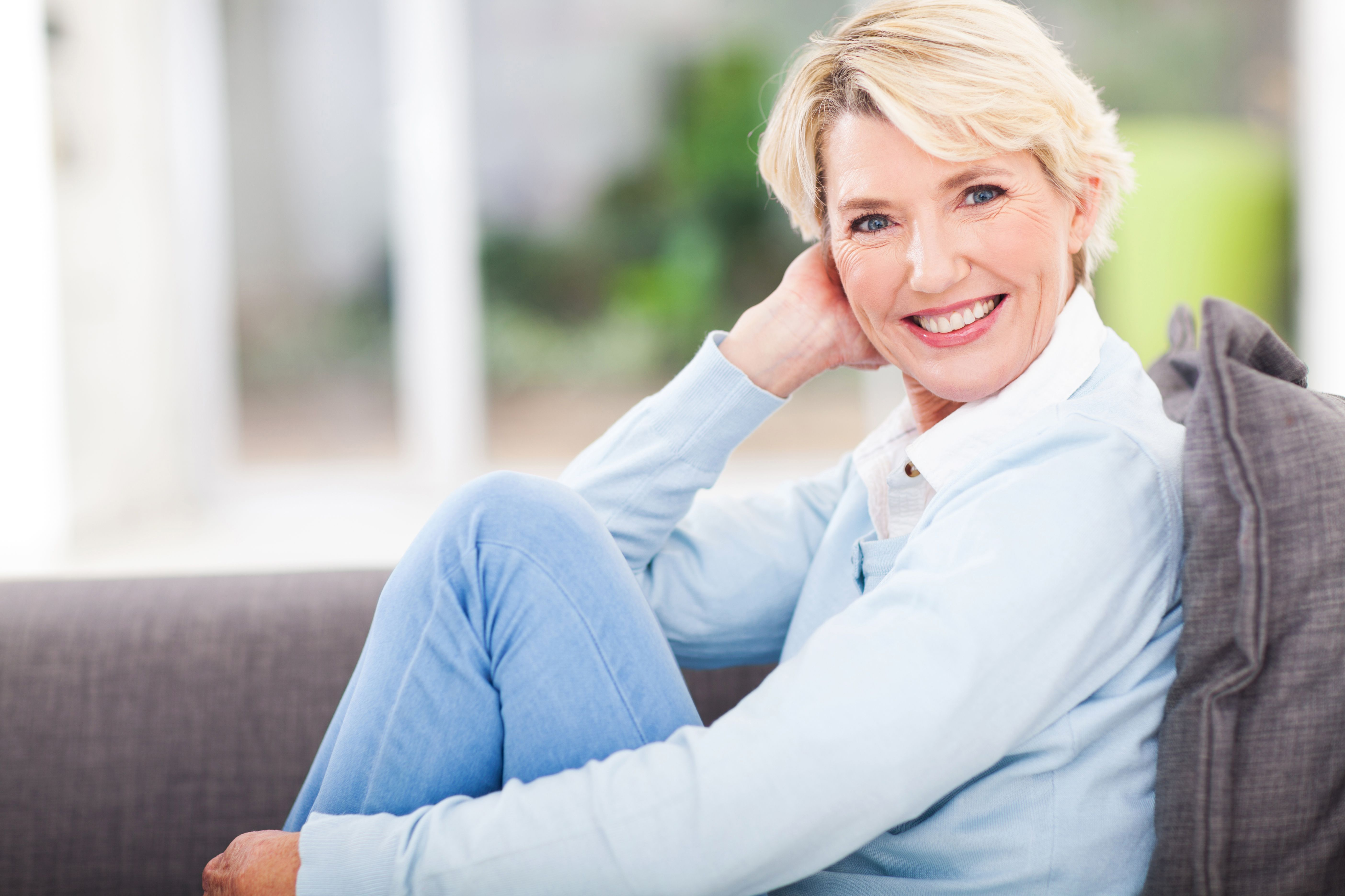 Mature Woman Sitting on Couch in a Blue Dress Shirt and Jeans