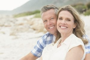 Mature Couple Smiling and Sitting on Beach